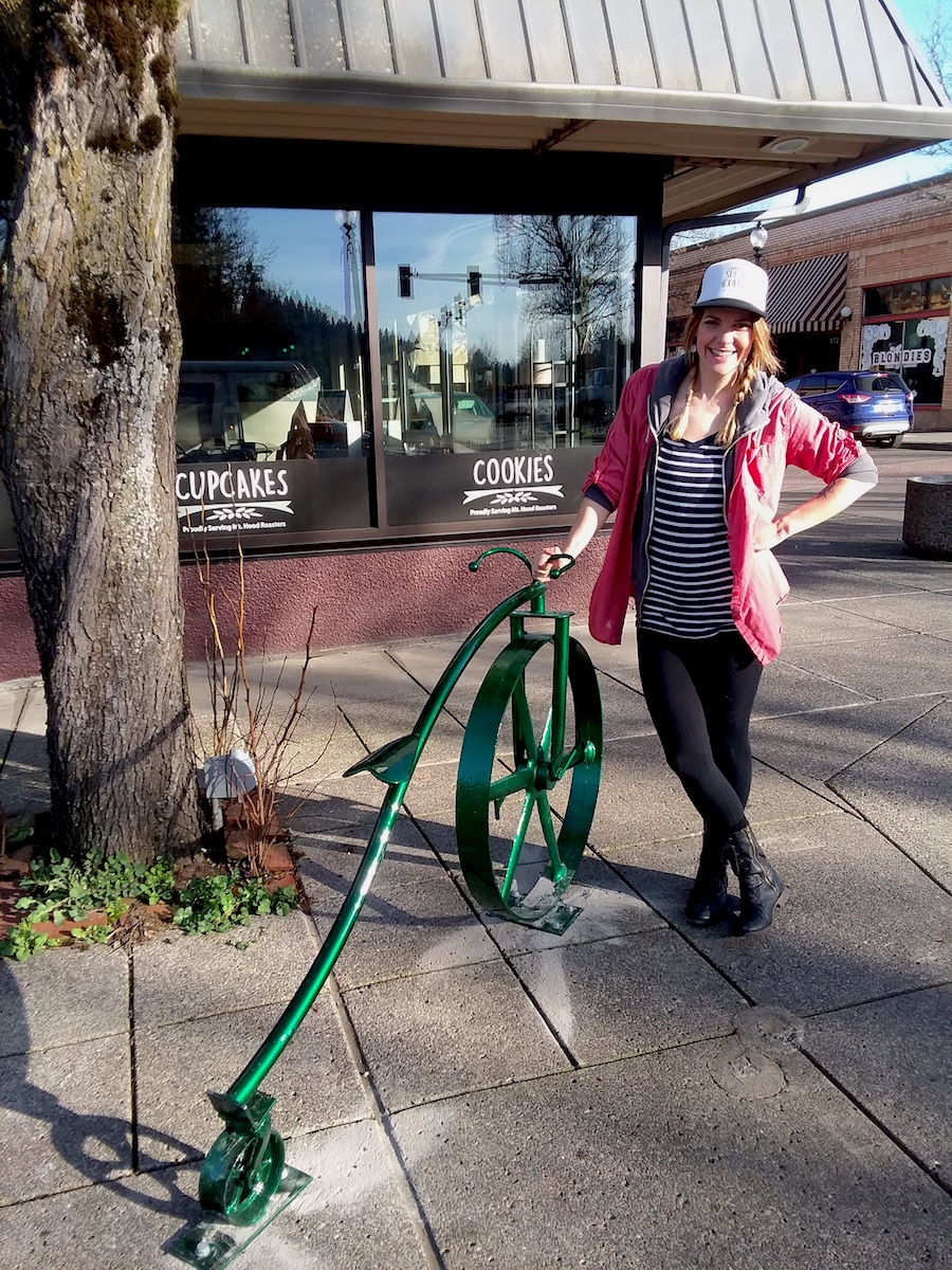 Kayla, owner of Sugar Cubed, poses with the new green bike rack on 1st and Main Ave.
